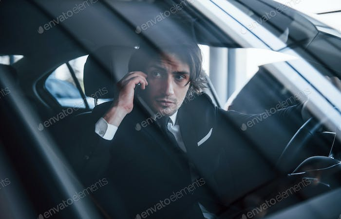 Young businessman in black suit and tie driving modern automobile