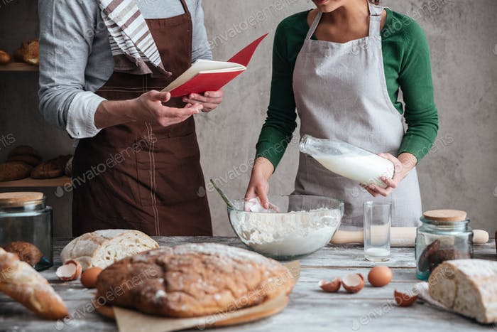 Cropped image of loving couple bakers cooking.
