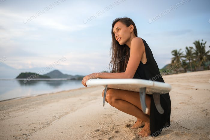 smiling happy excited active girl or woman holding surfboard