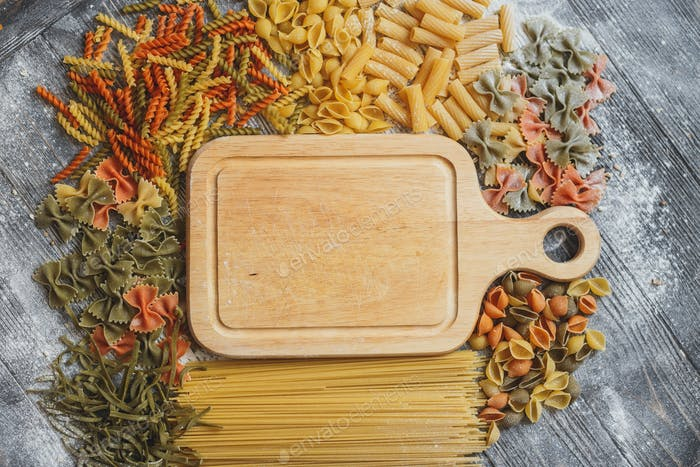 Mixed raw pasta with wooden board on old black  desk