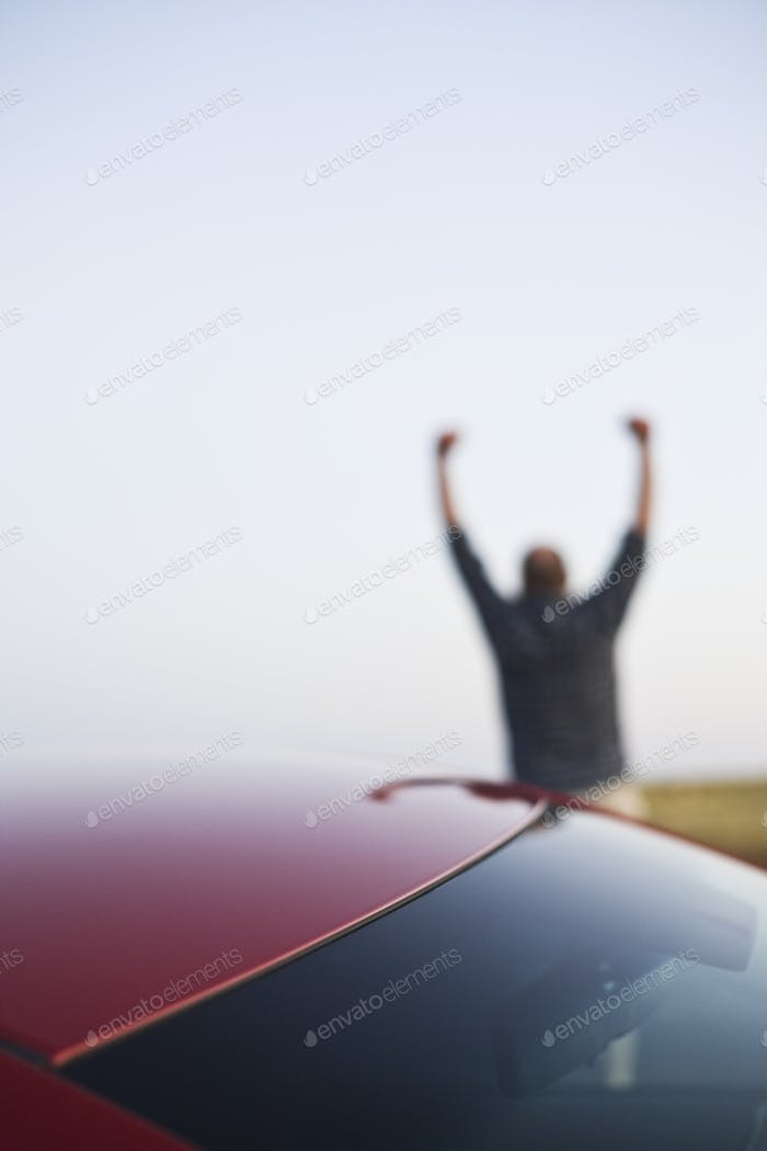 Closeup of a car window and a single male celebrating with his arms up in the background.