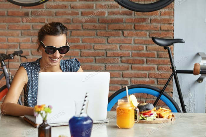 Female freelancer with happy smile working remotely on laptop. Successful food blogger typing new po