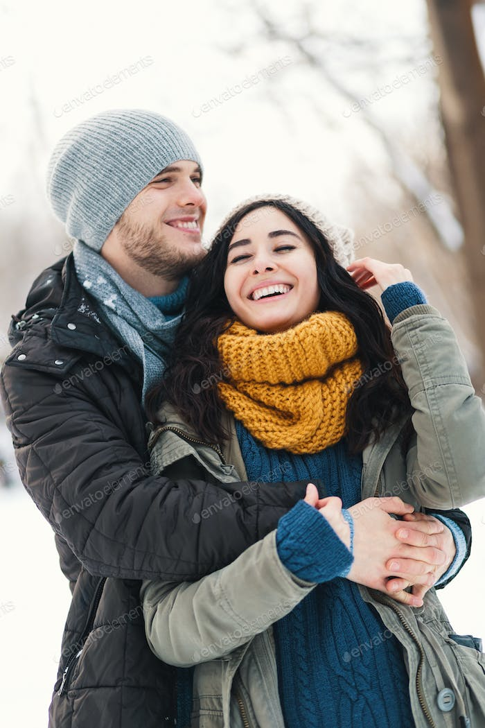 Happy young couple enjoying winter holidays smiling and hugging