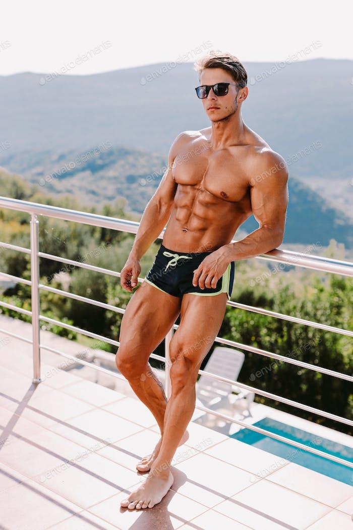 Schöner muskulöser Mann posiert im Freien ohne Shirtless und in Sonnenbrille