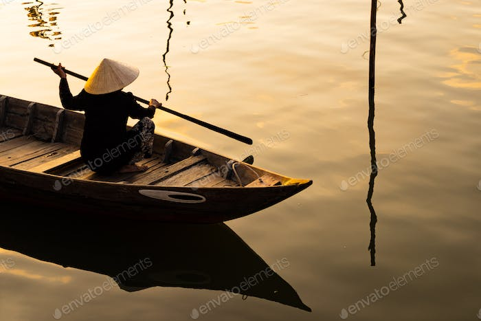 Vietnamese woman in traditional bamboo hat rowing