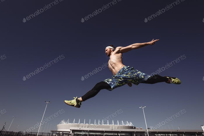 Young athletic man with a naked torso with headband dressed in the black leggings and blue shorts is