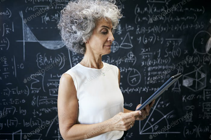 Middle aged academic woman working at blackboard
