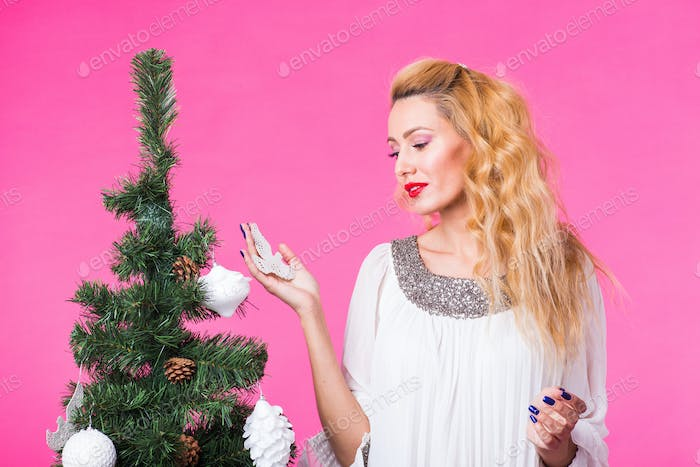 People, holidays and christmas concept - woman decorating christmas tree on pink background