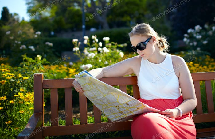 Girl reads the map outdoors