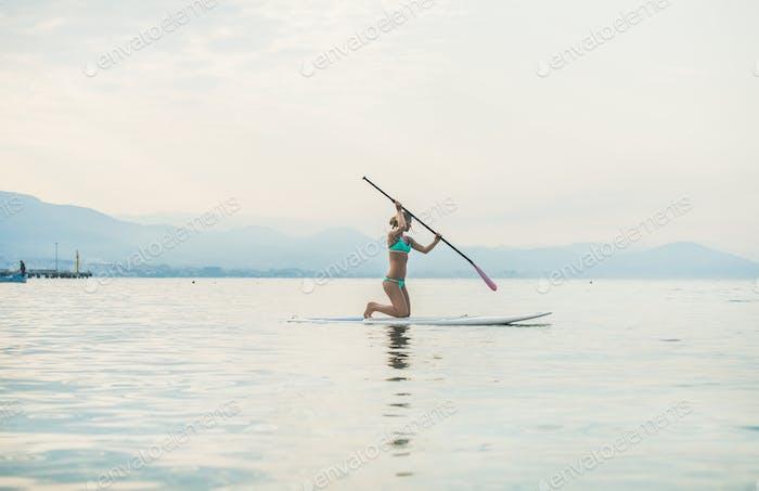 Young beautiful slavian woman tourist practicing paddle boarding
