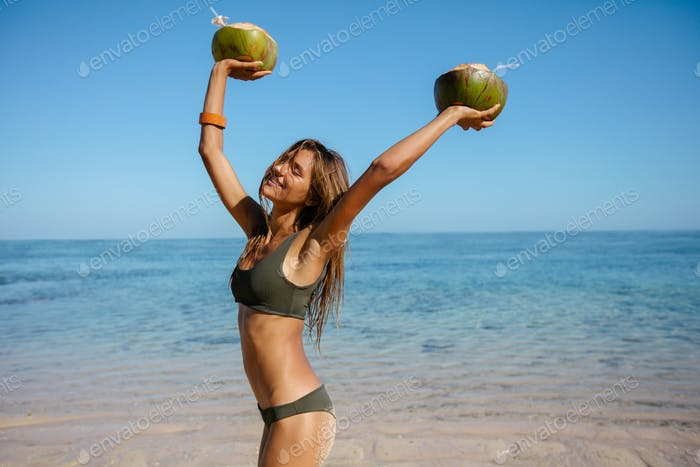 Young woman on the beach with fresh coconuts