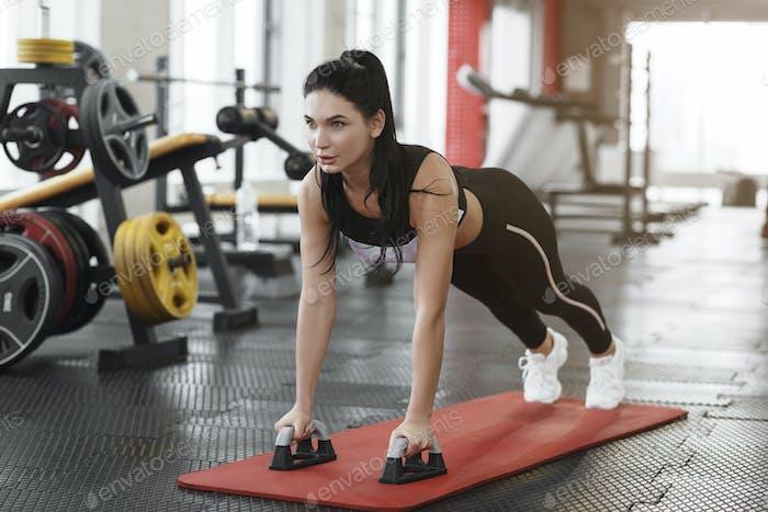 Sportkonzept Junge Frau tun Push-ups in der Turnhalle