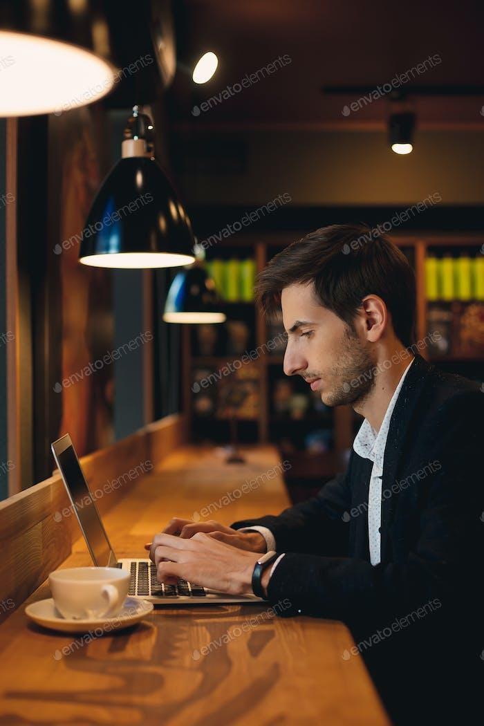 Hombre serio trabajando en la computadora portátil teniendo café