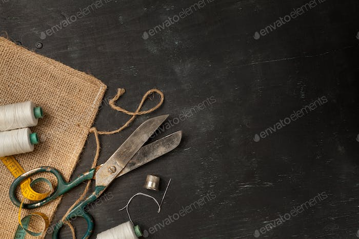 Retro sewing accessories on black wooden background