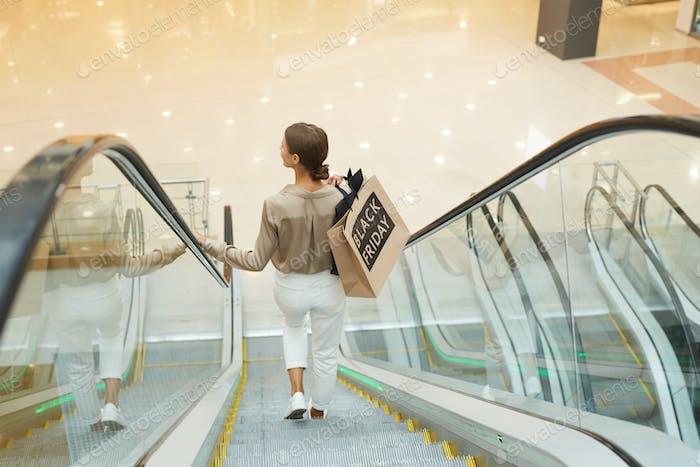 Frau stehend auf Rolltreppe