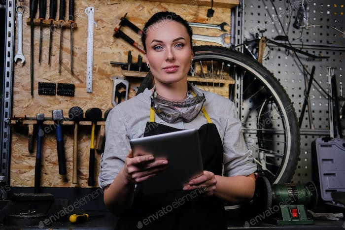 Beautiful brunette female wearing working clothes, apron and goggles, working in a workshop