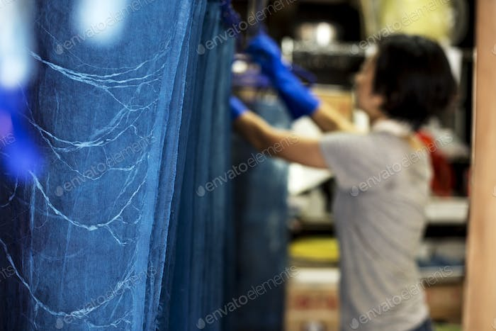 Japanese woman standing in a textile plant dye workshop, hanging up freshly dyed bright blue fabric.