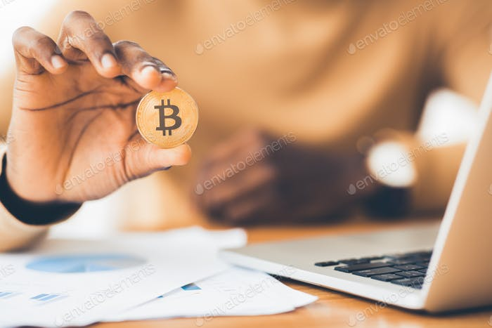 Unrecognizable african american guy showing golden bitcoin