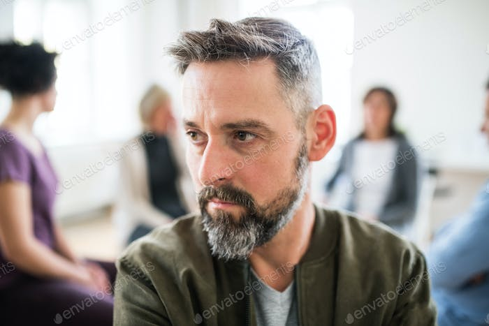 A portrait of senior depressed man during group therapy.