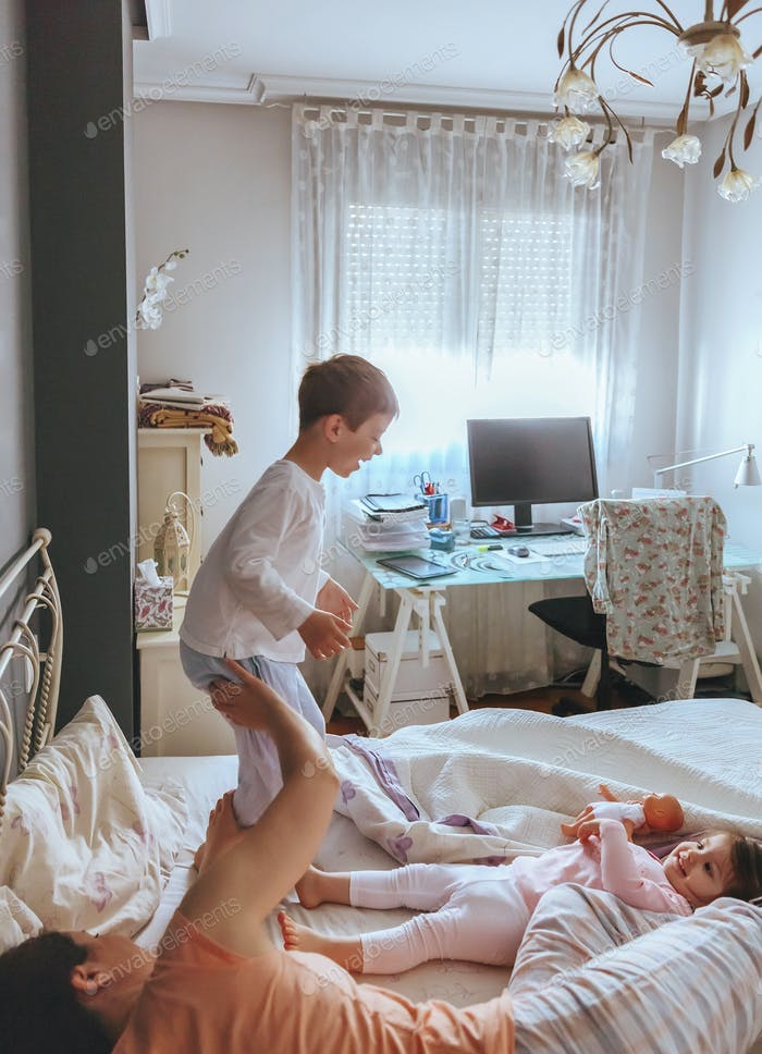 Boy jumping over the bed with his family