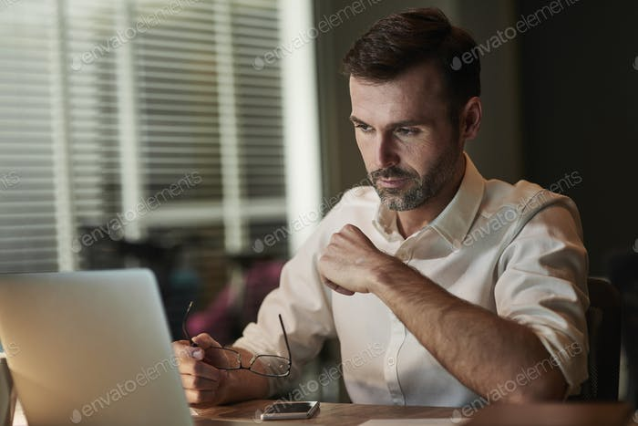 Focused businessman using a laptop at night