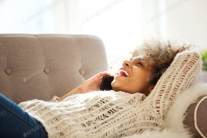 happy young woman talking on mobile phone and laughing at home
