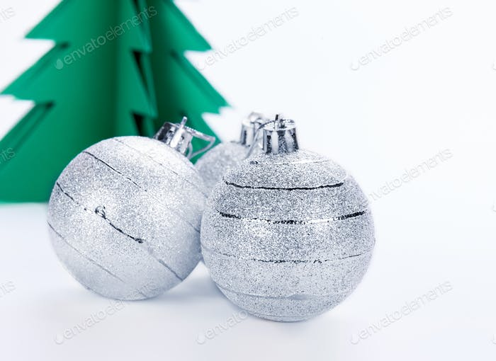 Christmas decorations and green paper tree on a white background