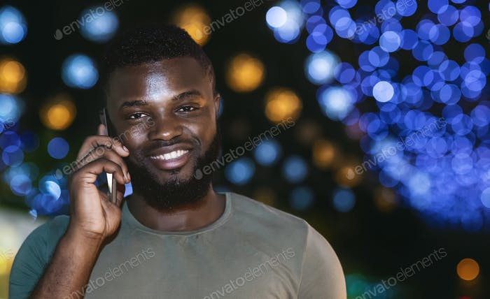 Cheerful afro guy talking on smartphone over night city background