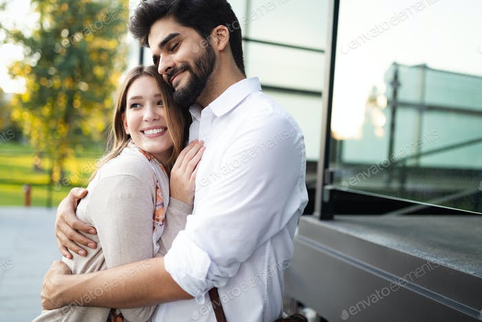 Happy young couple hugging and laughing outside