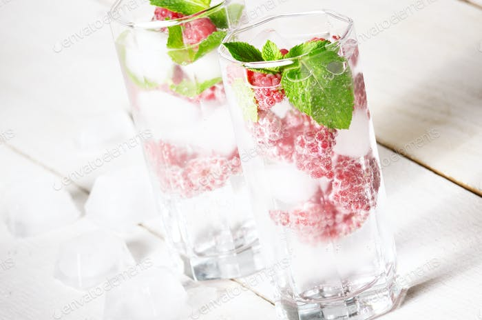 Raspberry Fruit Water with ice and mint on white table