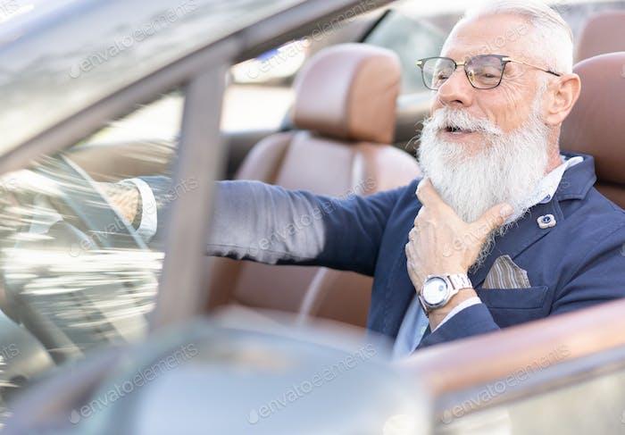 Senior business man driving a convertible car