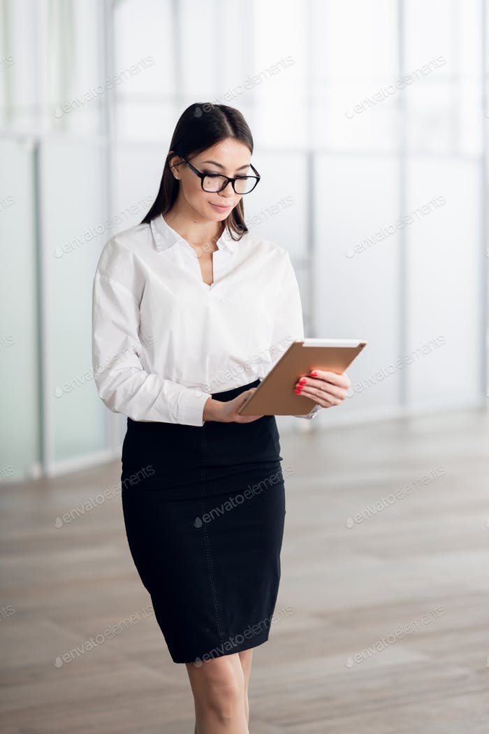 Attractive young woman wearing glasses and reading her touchscreen tablet while standing inside
