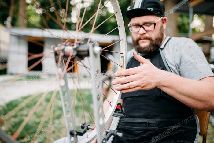 Mechanic adjusts bike spokes and repair wheel