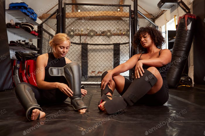 Two Female Mixed Martial Arts Fighters Putting On Protective Equipment Training In Gym