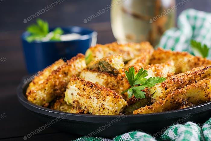 Gebackene Zucchini-Sticks mit Käse und Semmelbröseln. Vegane Lebensmittel. Vegetarische Küche.