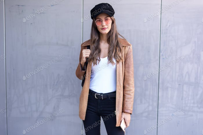 Pretty young woman looking at camera while standing in the street.