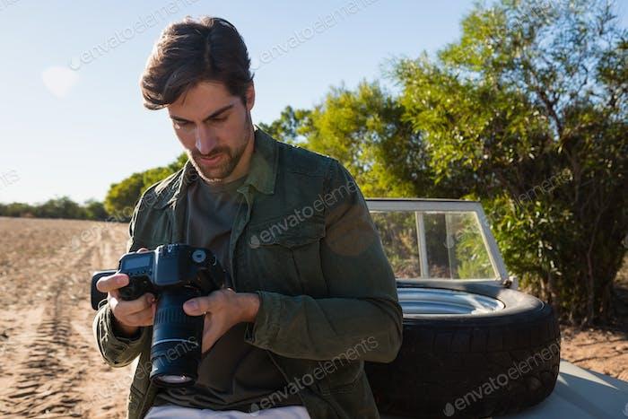 Man looking at camera while sitting on vehicle hood