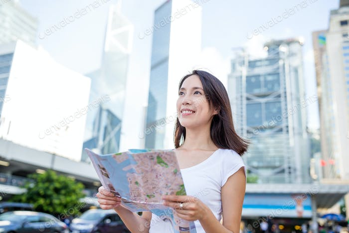Woman holding a city map in Hong Kong city