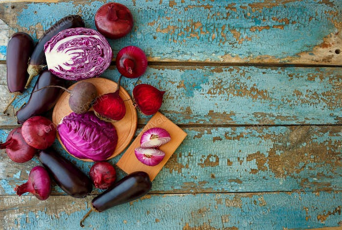Collection of fresh purple vegetables on the blue wooden backgro
