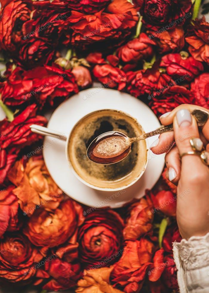 Womans Hand hält Löffel Espresso Kaffee über rote Blumen