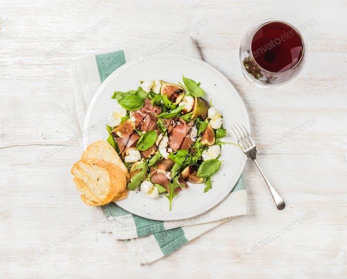 Prosciutto, arugula, basil, figs salad and glass of red wine