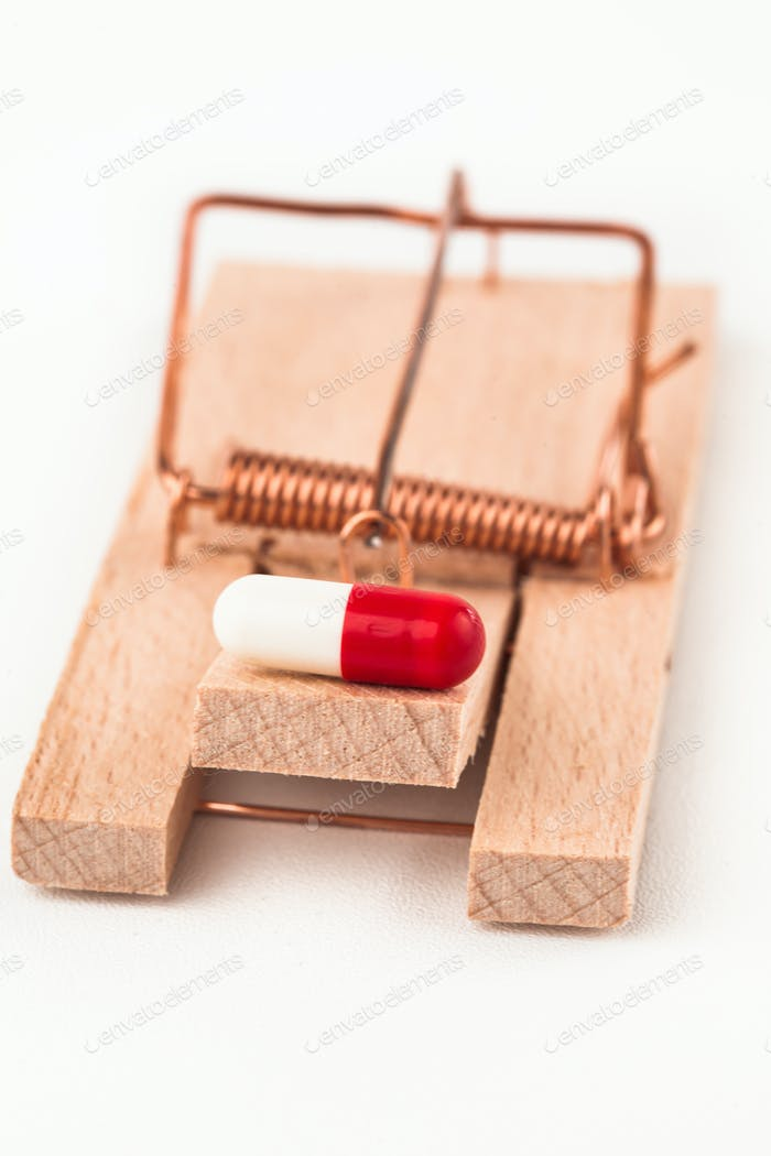 Pill in a mousetrap on white background