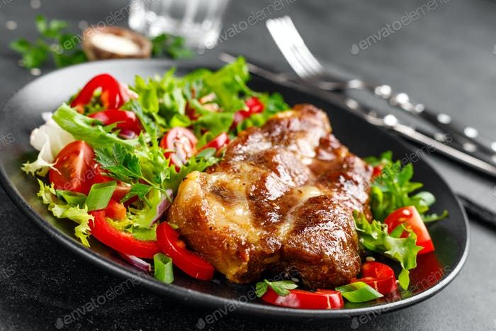 Baked pork steak with fresh vegetable salad on a plate