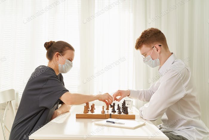 Two teenagers play chess during quarantine due to coronavirus pandemic. Boy and girl