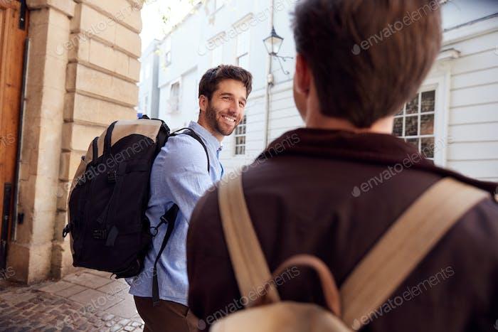 Rückansicht von Männlich Homosexuell Paar auf Urlaub tragen Rucksäcke Walking entlang City Street