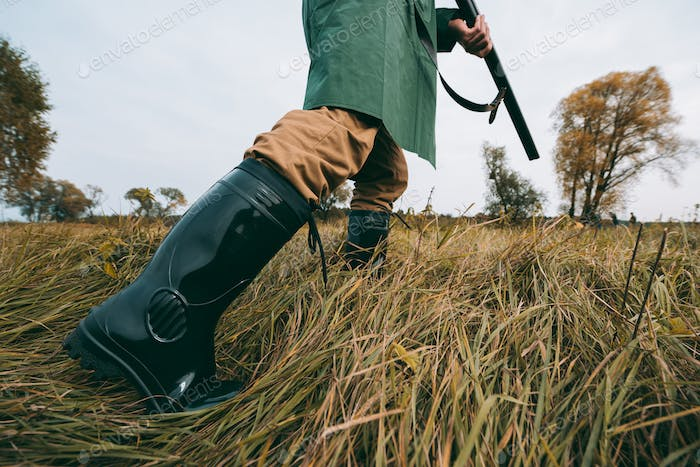 Cropped image of hunter going with a gun in a field