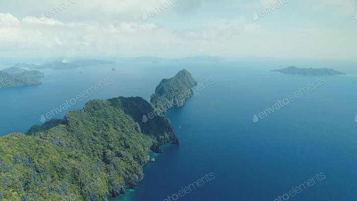 Tropical highland island aerial view at blue ocean bay. Asia mountainous isle with exotic nature
