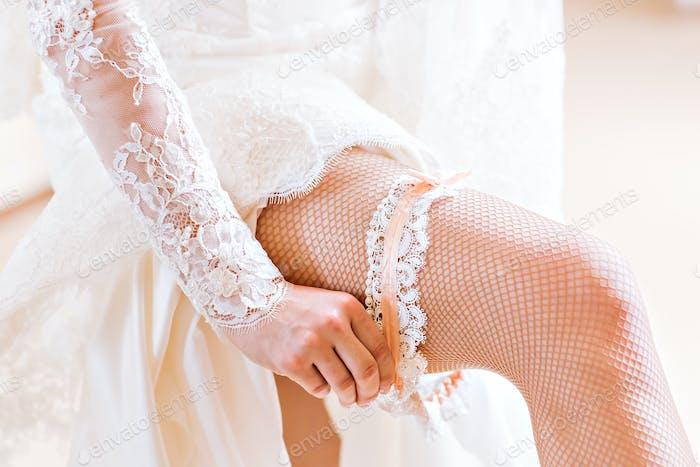 bride dresses garter on the leg.