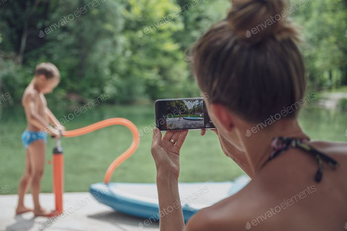 Young mother taking a photo of her son with mobile phone