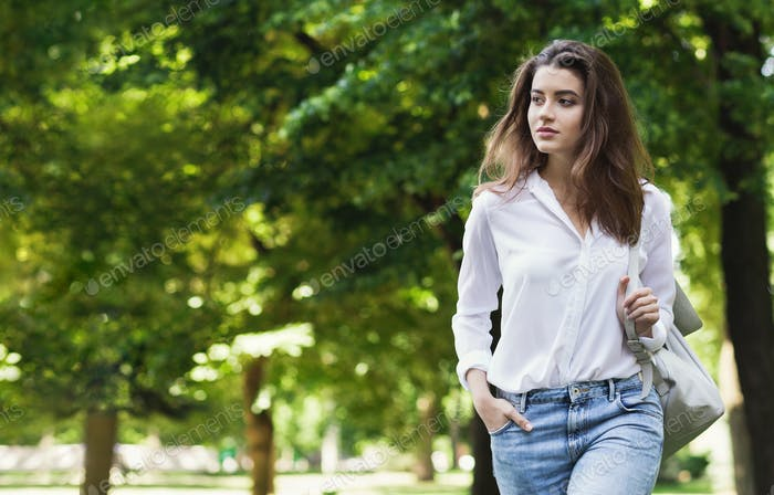 Casual woman walking alone through green park